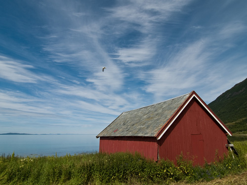 boatshed against a blue summer sky with some beautiful clouds