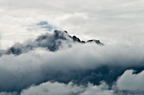 Photo of clouds hugging a Norwegian mountain peak