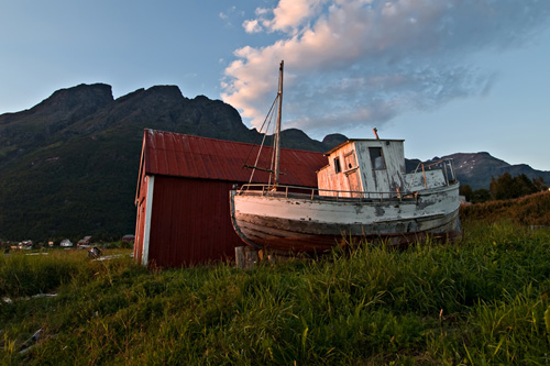 Photo of an old boat being lightened by a red sunset against a magnificent mountain