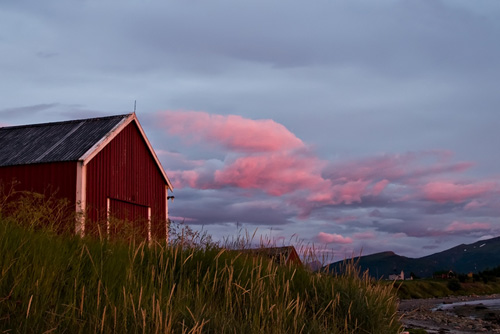 Photo of red sunset clouds and red boatshed