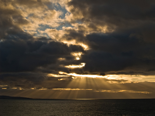 Photo of sunrays over the ocean in northern Norway