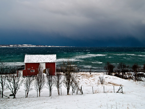 Picture of barn in Northern Norway against a stormy ocean