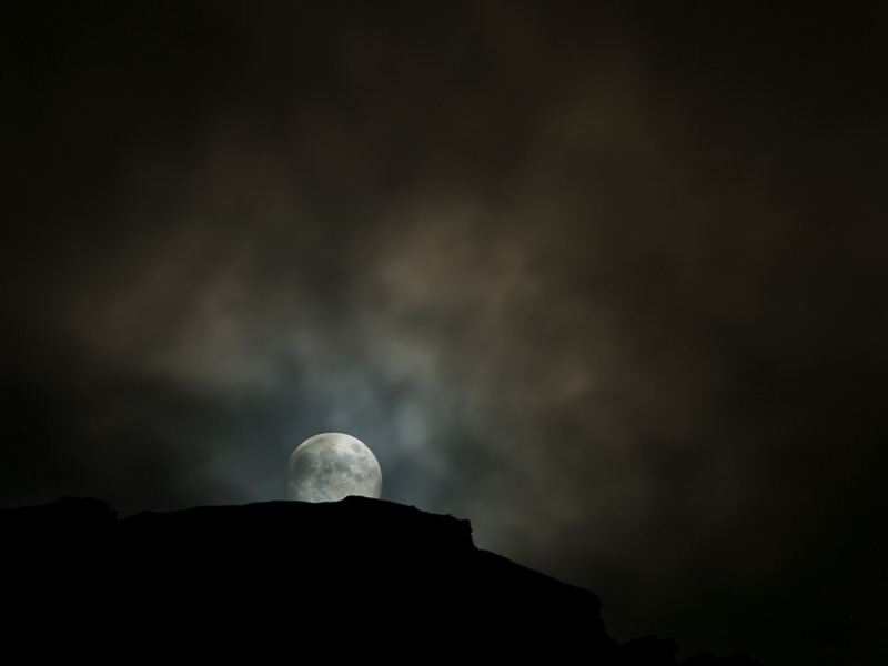 Picture of full moon rising and clouds above mountain in Northern Norway