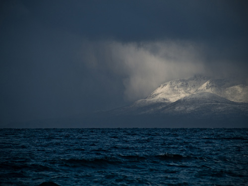 Photo of mountain being illuminated - Blizzard in northern Norway