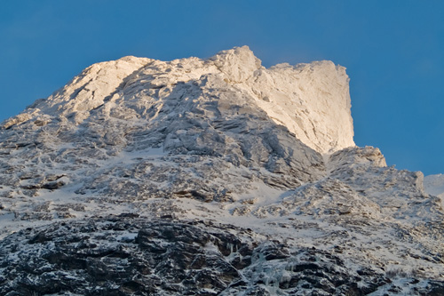 Picture of first sunlight shining on snow cowered mountain peak in Northern Norway