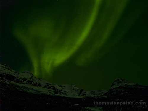 Picture of Northern Lights (Aurora Borealis) over snow-clad mountains in Northern Norway