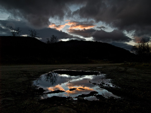 Photo of sunset reflection in a puddle