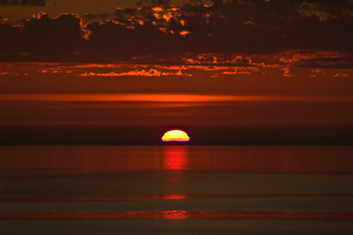 Photo of a red sunset where the sun disappears in the ocean
