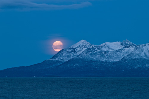 Picture of moon over a snow covered Senja