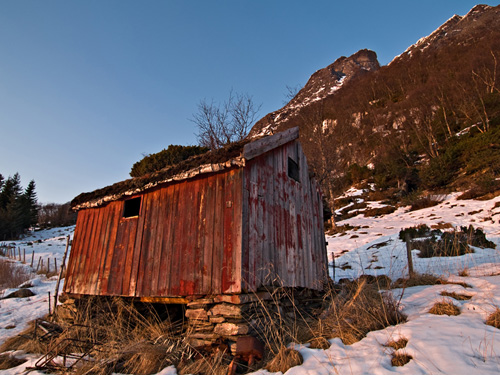 Photo of old Norwegian summer barn against mountain