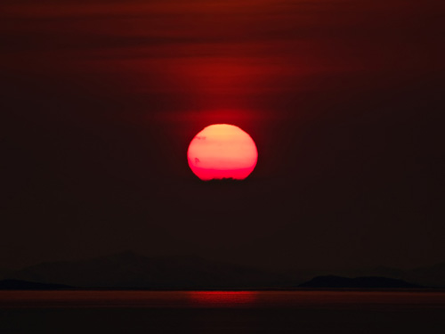 Zoomed in picture of the sun setting in the ocean in Northern Norway