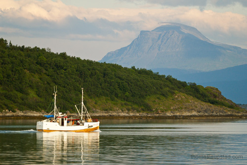 Photo of old wooden fishing boat on the sea by Harstad in Northern Norway